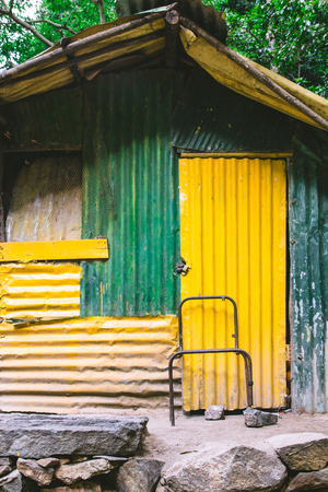 A shed or shack made of corrugated iron painted green and yellow found in the countryside outside Ella and Nuwara Eliya, Sri Lanka. Stock Photo