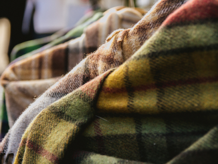 closeup of tartan shawls hung in a shop display for sale Stock Photo