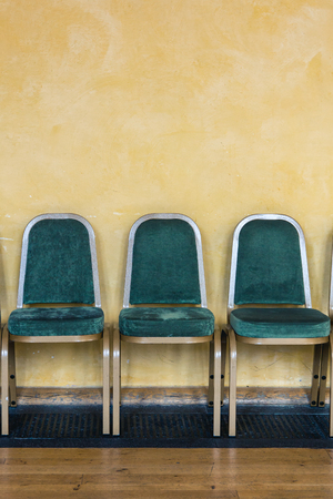Groene stoelen opgesteld tegen een gele muur in een wachtruimte Stockfoto