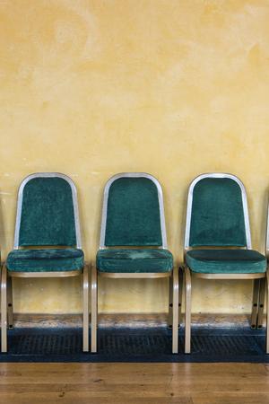 Sillas verdes alineadas contra una pared amarilla en un área de espera Foto de archivo - 91184430