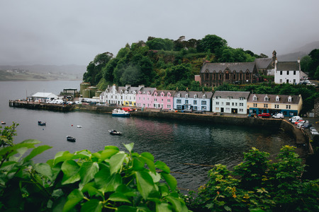 The row of pastel coloured houses in Portree harbour in gloomy weather Foto de archivo