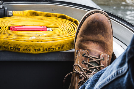 mens foot wearing tough boots and jeans on board a ship with a fire hose