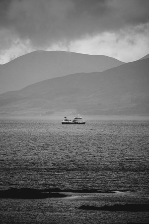A fishing boat heads out to sea in stormy weather. Isle of Skye, Scotland.