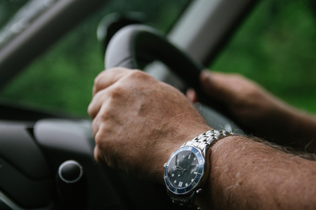 A man with both hands safely on the steering wheel, right hand drive united kingdom