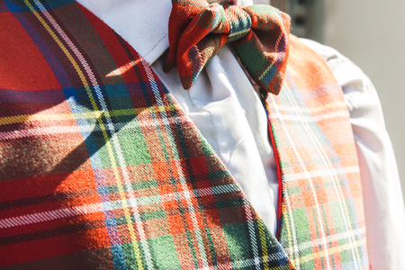 closeup of matching tartan bowtie and waistcoat outdoors in the warm sunlight with a white shirt menswear clothing Imagens