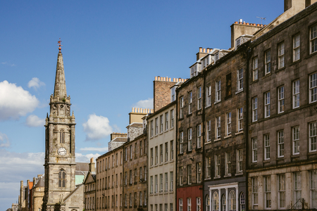 Looking up at a row of houses and church steeple in an Edinburgh (Scotland) street on a beautiful sunny day