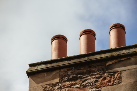 Chimney stack with three chimneys of an old traditional English house in the city of edinburgh, Scotland