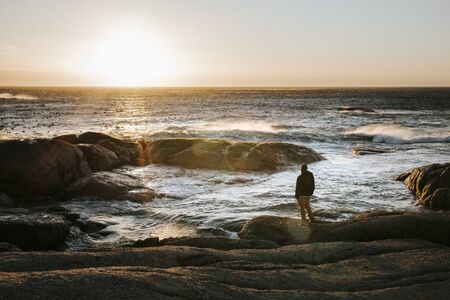 Adult male looking off into the distant ocean at sunset. Calm and peace, inspirational scene.