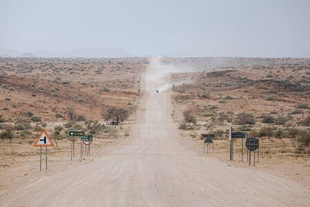 Cars kick up dust on the C35 gravel road in Tsiseb region, Namibia, Africa