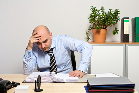 Manager looks demotivated in his files Standard-Bild