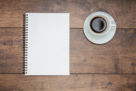 Notepad and fresh coffee on a wooden table Standard-Bild