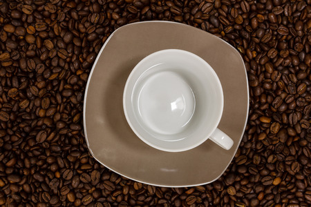 Empty cup on brown coffee beans
