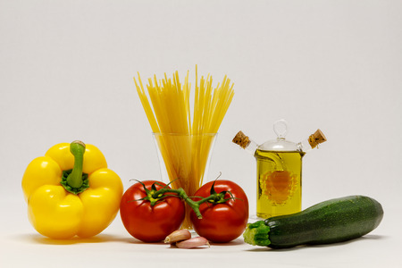 Peppers, tomatoes, zucchini and cooking oil on white background