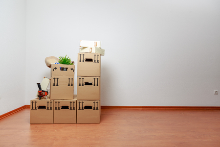 Boxes in front of a white wall in the new home Standard-Bild