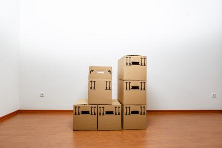 Boxes in empty white room on wooden parquet Standard-Bild