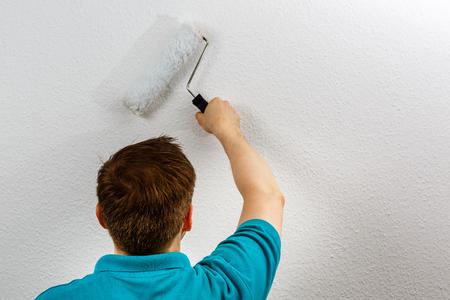 Man paints wall white, close up Standard-Bild