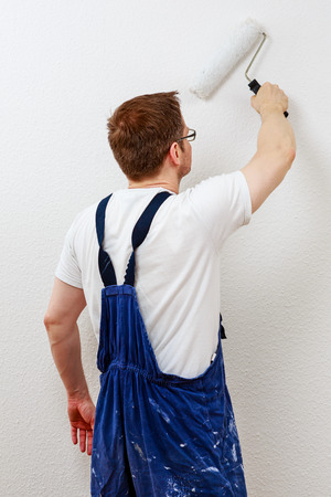 Man in blue overall painting a wall white