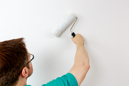 Man paints wall in white, close up Standard-Bild