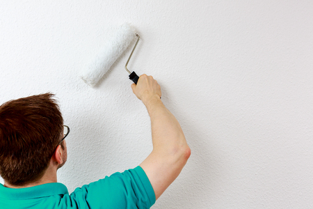 Man paints wall in white, close up 版權商用圖片