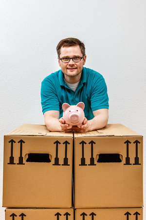 happy man holds his piggy bank high, in his new apartment. Standard-Bild - 122184909
