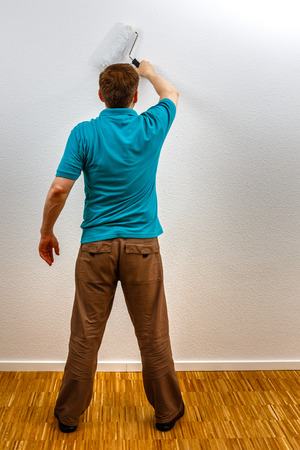 Man paints wall in white, vertical format Standard-Bild
