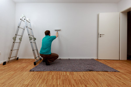 Man painting a wall in white Standard-Bild - 122184914