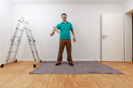 Man paints on imaginary concept panel in an empty room Standard-Bild - 122184916