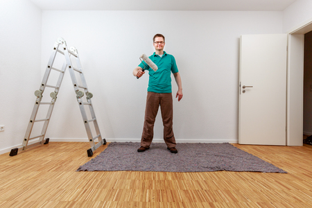 Man paints on imaginary concept panel in an empty room Standard-Bild - 122184923