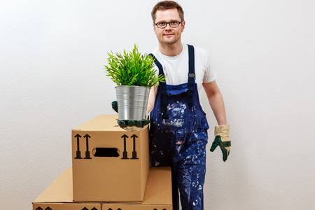 man in blue overall presenting a green plant