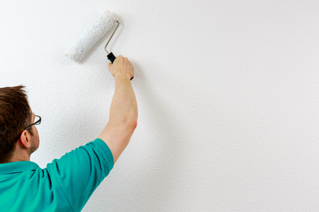 Man paints wall in white, close up Standard-Bild - 122184933