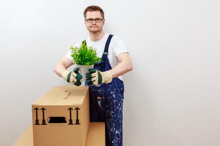 man in blue overall presenting a green plant Standard-Bild - 122184934