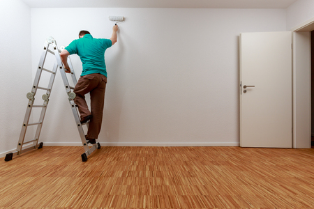 Man on ladder while painting the wall
