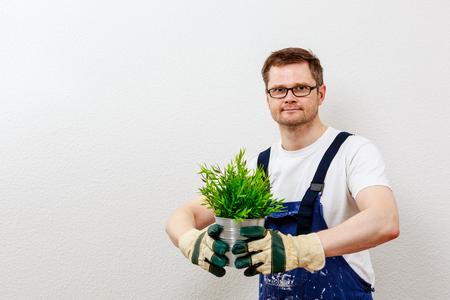 man in blue overall presenting a green plant Standard-Bild - 122184940