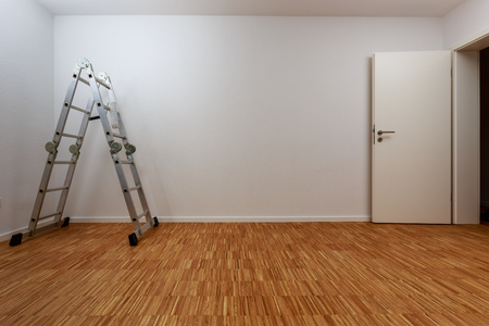 Empty, clean white room with aluminum ladder