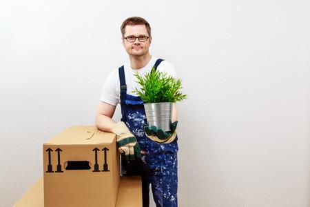 man in blue overall presenting a green plant Standard-Bild - 122184944