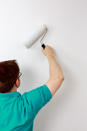 Man paints wall in white, close up Zdjęcie Seryjne
