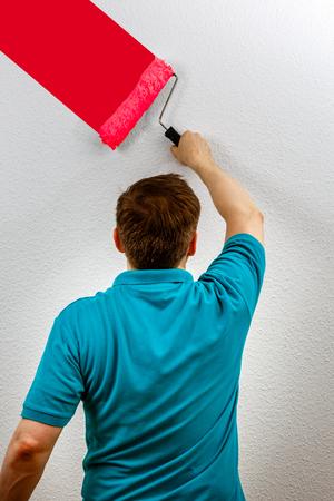 Man paints wall red, close up Standard-Bild