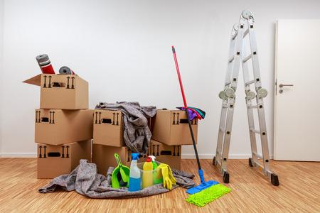 Stanza pulita e bianca con cartoni e strumenti per la pulizia