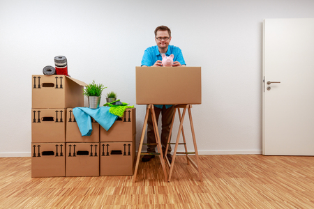 Man is leaning on the carton with his piggy bank in his hands