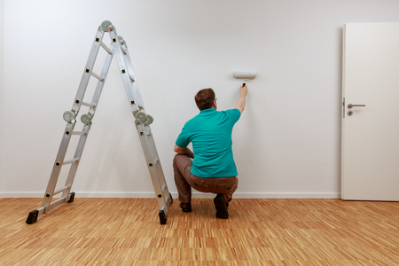 Man is painting a wall white Standard-Bild - 122186272