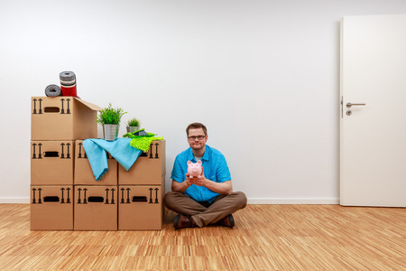Man is sitting on the parquet floor with his piggy bank in his hands