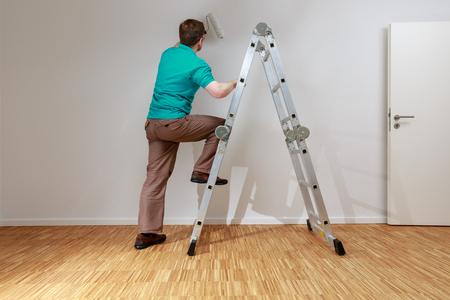 Man is painting a wall white Standard-Bild - 122186966