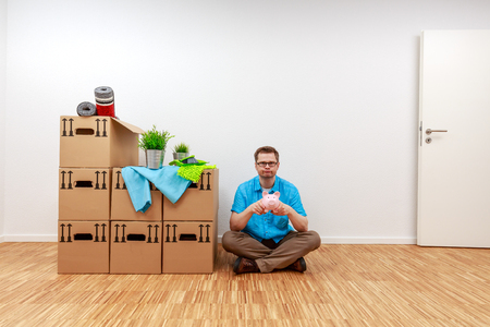 Man looks disappointed at his empty piggy bank in his hands Standard-Bild