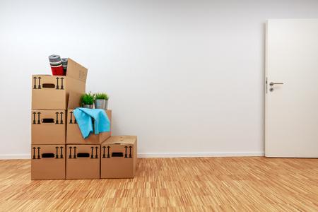 Umzugskartons im leeren weißen Raum mit Holzparkett