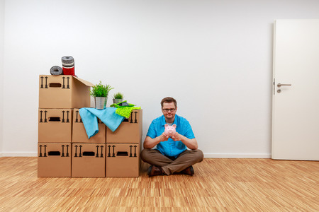 Man is sitting on the parquet floor with his piggy bank in his hands Standard-Bild - 122186973