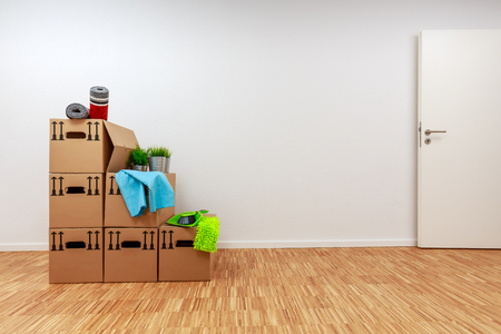 Moving cartons in empty white room with wooden parquet