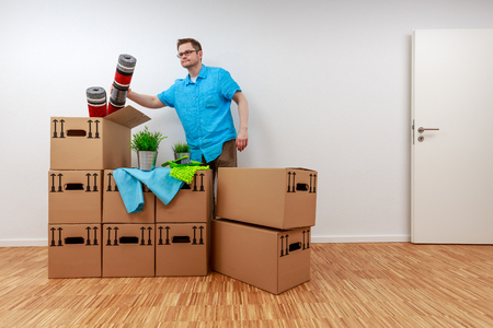 Man empties moving boxes Standard-Bild - 122186975