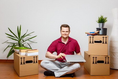 Young man using laptop in his new home Standard-Bild - 122186994