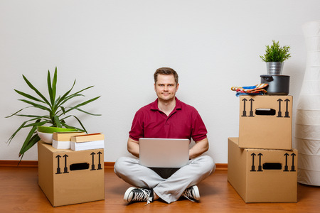 Young man using laptop in his new home