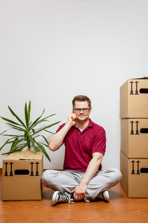Man sits on the floor and talks on mobile phone Standard-Bild